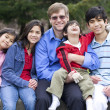 Happy interracial family enjoying day at park with disabled son — Stok fotoğraf