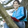 Preteen girl sitting in tree writing in journal or notebook — Stock Photo