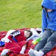 Teenager caring for disabled child at park — Stock Photo