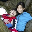 Sister holding disabled brother in tree — Stock Photo