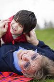 Padre jugando con hijo discapacitado en pasto en el parque — Foto de Stock