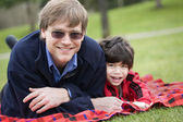Father lying on blanket with disabled son at park — Stock Photo
