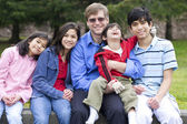 Happy interracial family enjoying day at park with disabled son — Stock Photo