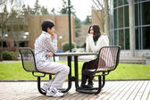 Two young teenagers sitting talking together outdoors — Stock Photo