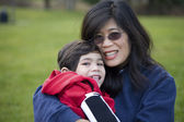 Beautiful asian mother holding her disabled son at park — Stock Photo