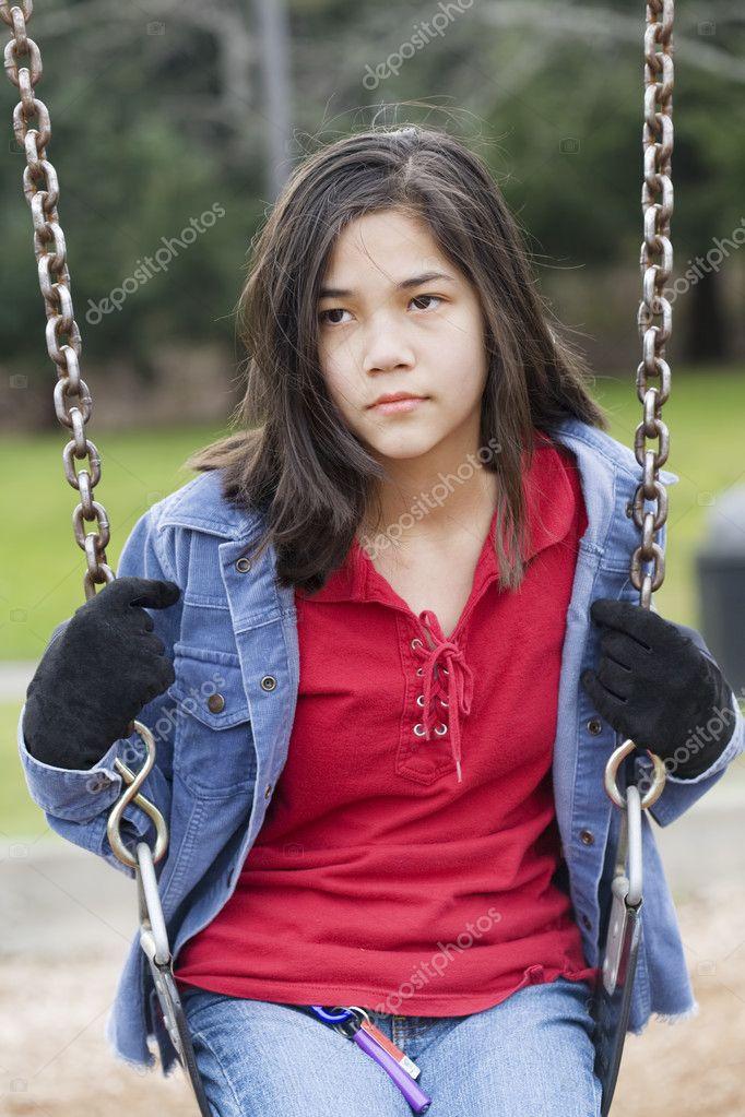 Angry, sad preteen girl sitting on swing - Stock Image