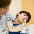 Father holding disabled son in doctor's office - Stockfoto