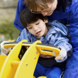 Father helping disabled son play on playground equipment — Stock Photo #6104847