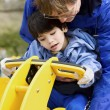 Father helping disabled son play on playground equipment — Stock Photo