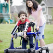 Stock Photo: Big sister helping younger disabled brother in walker