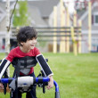 Disabled four year old boy standing in walker near a playground - Zdjęcie stockowe