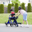Big sister helping younger disabled brother in walker — Stock Photo