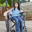 Young girl in wheelchair in front of stairs — Stock Photo #6104882