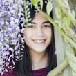 Stock Photo: Beautiful young teen girl standing under wisterivines