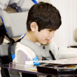 Disabled four year old boy studying or reading in wheelchair — Foto Stock