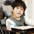 Disabled four year old boy studying or reading in wheelchair — Foto de Stock