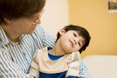 Father holding disabled son in doctor's office — Stock fotografie