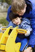 Pai ajudando deficientes filho brincar em equipamentos de playground — Fotografia Stock