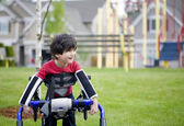 Disabled four year old boy standing in walker near a playground — Foto de Stock