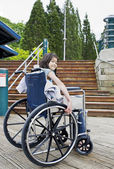 Young girl in wheelchair in front of stairs — Stock Photo