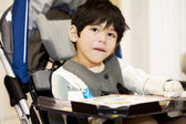 Disabled four year old boy studying or reading in wheelchair — Stock Photo