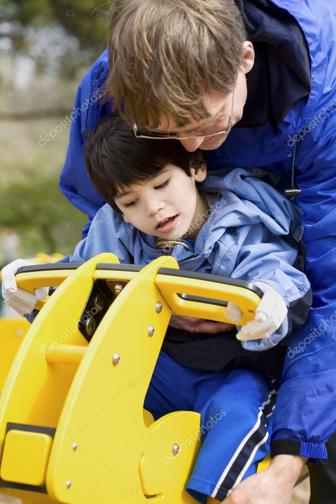 Father helping disabled son play on playground equipment  Stock Photo #6104847