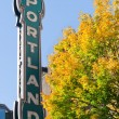 Portland Oregon neon sign with fall trees - Stock Photo