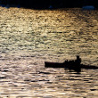 Stock Photo: Lone man in kayak as silhouette at sunset