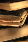 Old grungy books closeup in sepia shallow DOF — Stock Photo