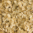 Stock Photo: Oatmeal background, rolled raw oats macro closeup