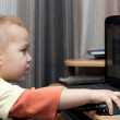 Cute baby boy playing with laptop — Stock Photo