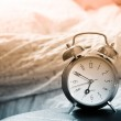 Clock and bed showing wake time in bedroom — Stock Photo #5857446