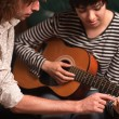 Young Musician Teaches Female Student To Play the Guitar — Stock fotografie #5422327