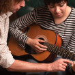 Young Musician Teaches Female Student To Play the Guitar - Foto Stock