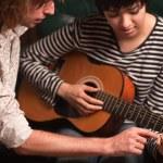 unga musiker undervisar kvinnlig student att spela gitarr — Stockfoto