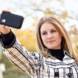 Pretty Young Woman Taking Picture with Camera Phone - Stock Photo
