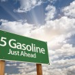 5 Gasoline Green Road Sign and Clouds - Stock Photo