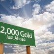 2,000 Gold Just Ahead Green Road Sign and Clouds - Stock Photo