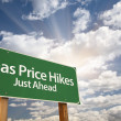 Gas Price Hikes Green Road Sign and Clouds - Stock Photo