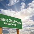 Insane Gas Prices Green Road Sign and Clouds - Stock Photo
