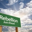 Rebellion Green Road Sign and Clouds - Stock Photo
