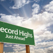 Record Highs Green Road Sign and Clouds - Stock Photo