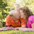 Royalty-Free Stock Photo: Affectionate Couple Kiss as Cute Son Looks On
