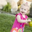 Smiling Young Girl in The Park Holding Apple - Stock Photo