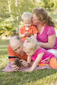 Young Family Talking about Pine Cones in Park — Stock Photo