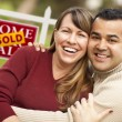 Mixed Race Couple in Front of Sold Real Estate Sign - Stock Photo