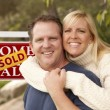 Happy Couple in Front of Sold Real Estate Sign — Stock Photo #5672924