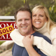 Stock Photo: Happy Couple in Front of Sold Real Estate Sign