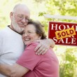 Senior Couple in Front of Sold Real Estate Sign - Stock Photo