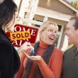 Hispanic Female Real Estate Agent Handing Keys to Excited Couple — Stock Photo #5672928